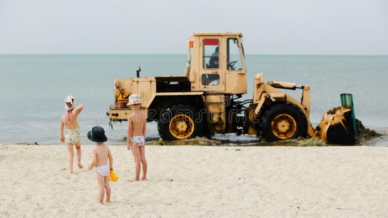 Plage de nettoyage de tracteur pendant le début de la matinée des déchets rempli photos stock