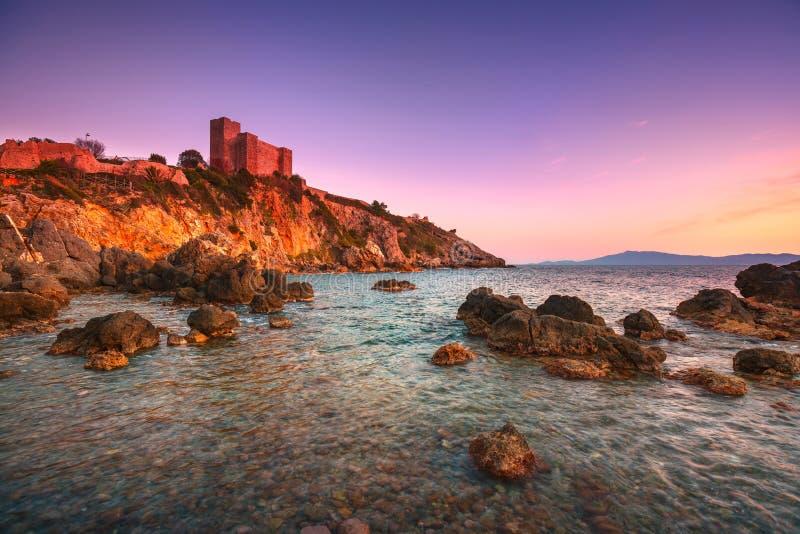 Plage de roche de Talamone et forteresse médiévale au coucher du soleil Maremma Arg photographie stock libre de droits