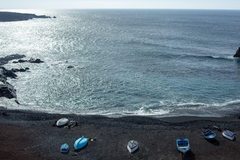 Plage de sable et bateaux de pêche noirs uniques à l'EL Golfo, Lanzarote, Îles Canaries photographie stock libre de droits