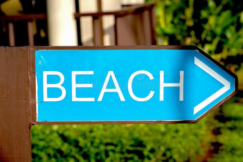 Plage de Signpost, en bois, vert, route vers la plage sur la droite, sur le fond de la route et les plantes vertes des image stock