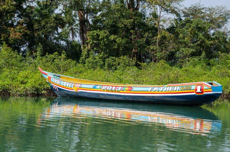 Plage de Tokeh, Sierra Leone - 6 janvier 2014 : Le beau et coloré bateau en bois peint de pirogue a amarré dans les palétuviers photos libres de droits