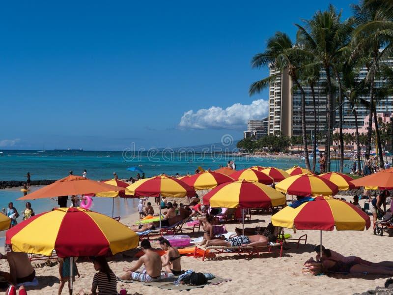 Plage de Waikiki avec les parapluies jaunes rouges images stock