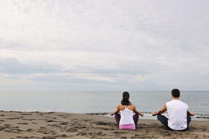 Plage de yoga de couples image libre de droits