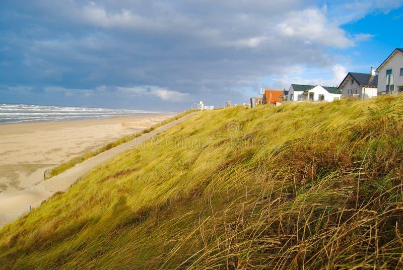 Plage, dune avec l'herbe et maisons photographie stock libre de droits