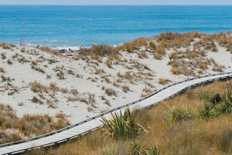 Plage en bois de sable de promenade au-dessus d'horizon de côte photo stock