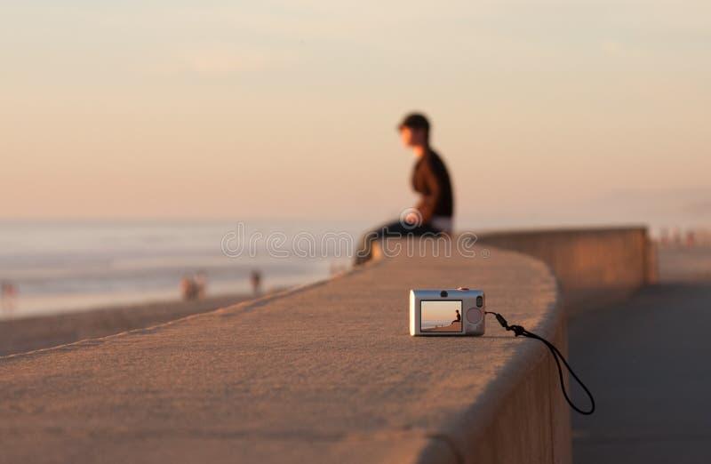 Plage et appareil-photo se reposants de coucher du soleil d'homme seuls photos libres de droits
