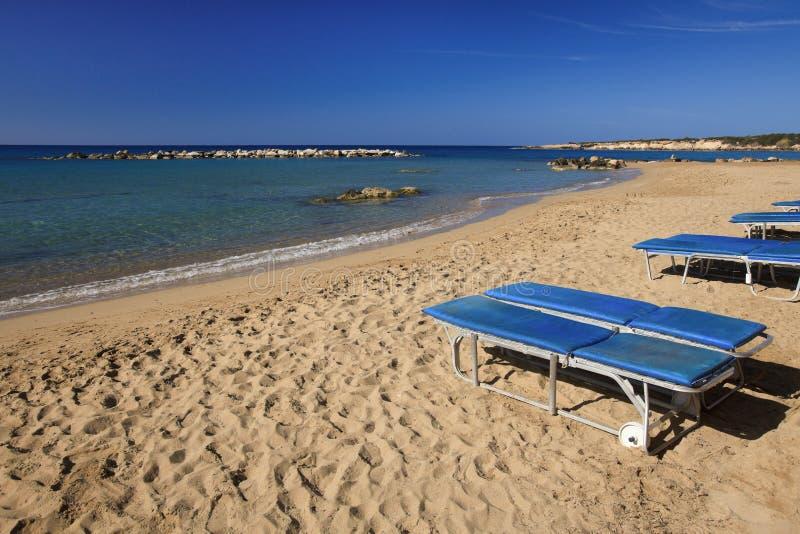 Plage et chaises longues de Coral Bay en Chypre photo stock
