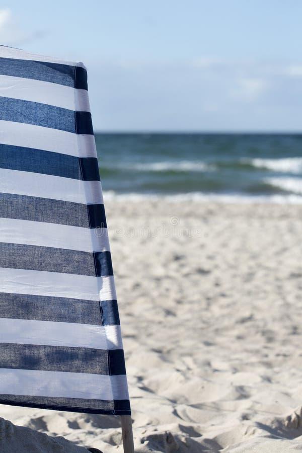 Plage et coupe-vent blanc bleu photos libres de droits