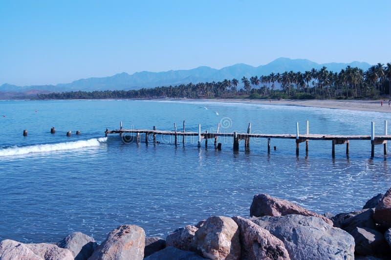 Plage et vieux pilier de pêche le long de littoral photos stock