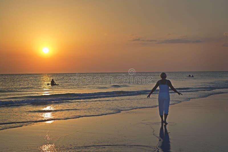 Plage flânant au coucher du soleil images libres de droits
