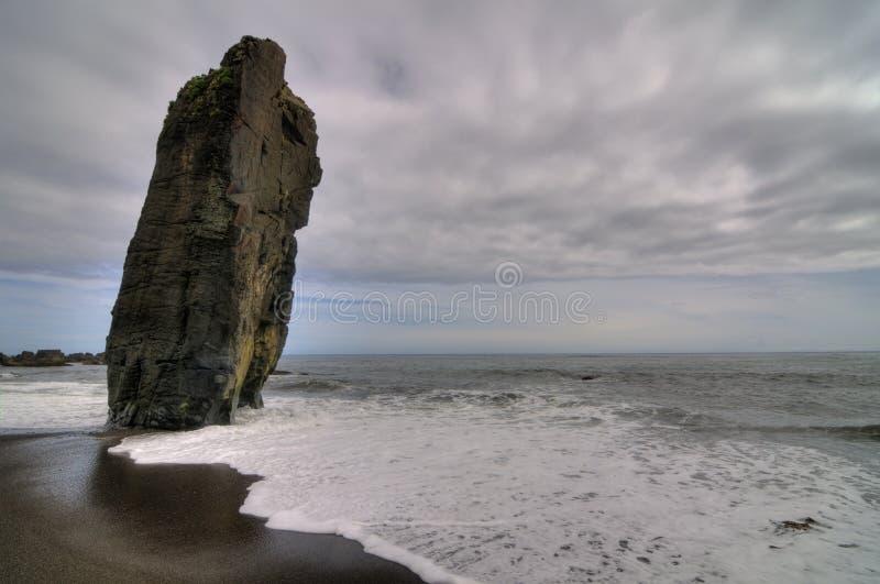 Plage isolée avec une grande roche inclinée images stock