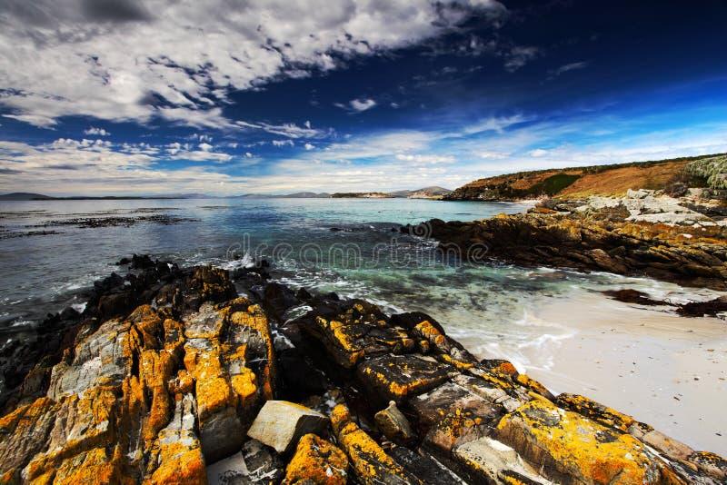 Plage jaune de roche et de sable au lever de soleil Coûtez avec la vague bleu-foncé et les nuages blancs sur le ciel bleu Coût ro photo stock