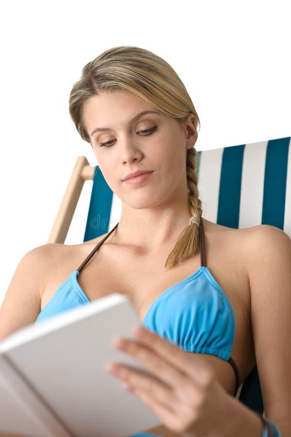 Plage - jeune femme heureux dans le bikini avec le livre images stock