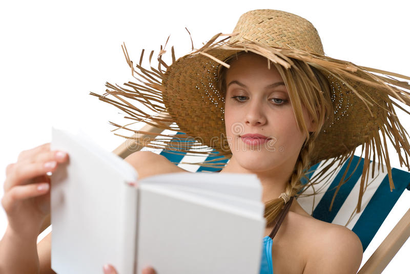Plage - la jeune femme détendent avec le livre dans le bikini image libre de droits