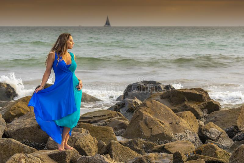 Plage latine de Poses Outdoors On A de modèle de belle brune au coucher du soleil images stock