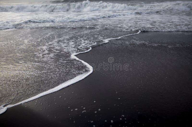 Plage noire de sable dans l'Océan Indien image stock