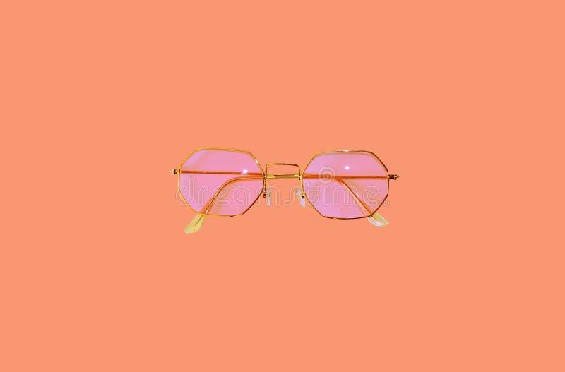 Plage réglée sur le fond de pêche Articles des accessoires des femmes Concept de vacances d'été Modèle rose de lunettes de soleil images libres de droits