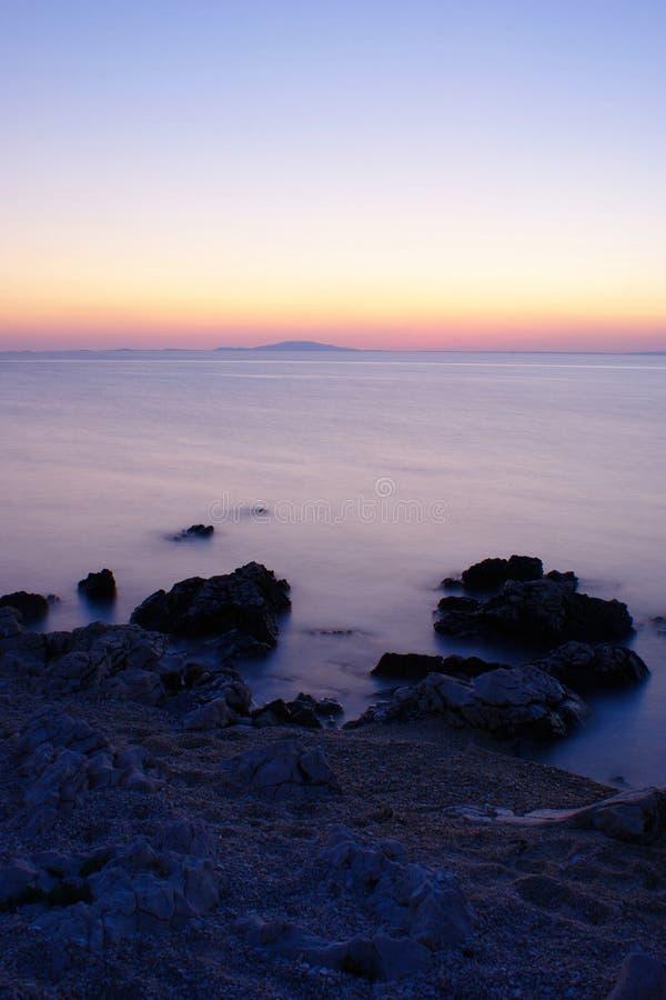Plage rocheuse sur l'île de PAG après coucher du soleil photos stock