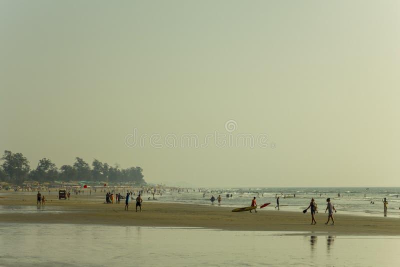Plage sablonneuse de mer le soir contre le contexte des huttes et des arbres, beaucoup de personnes marchant à la plage et nagean image stock