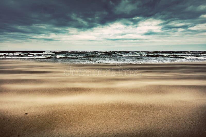 Plage sablonneuse le jour orageux par la mer photo libre de droits