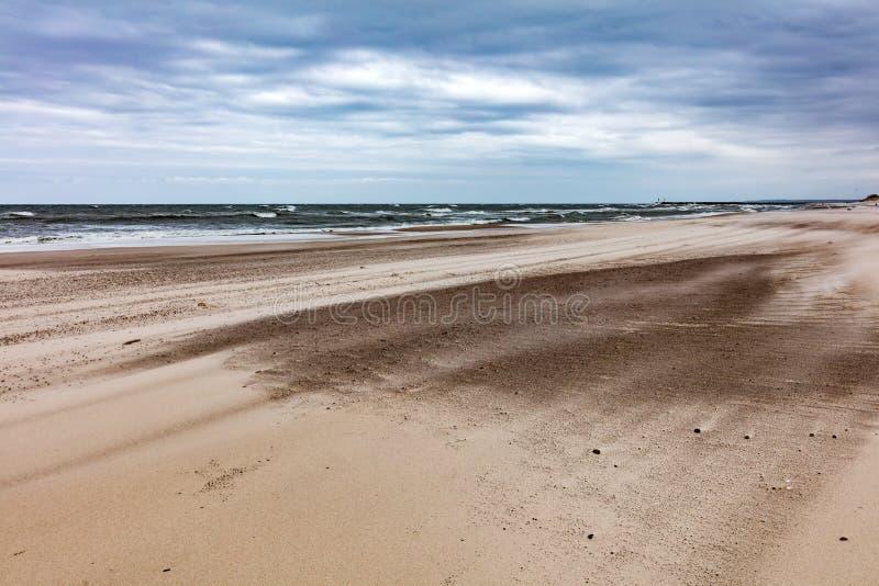 Plage sablonneuse le jour orageux par la mer photos stock