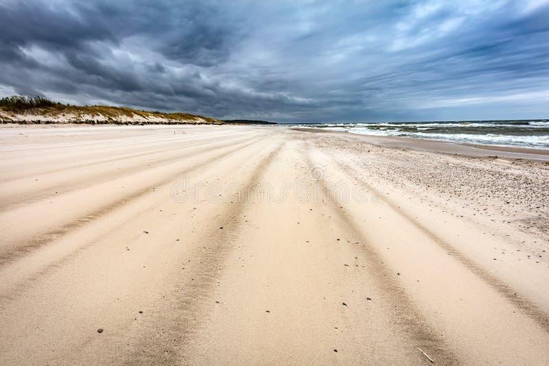 Plage sablonneuse le jour orageux par la mer photo stock