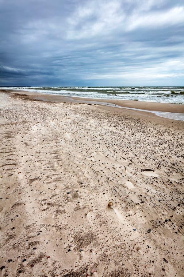 Plage sablonneuse le jour orageux par la mer image libre de droits