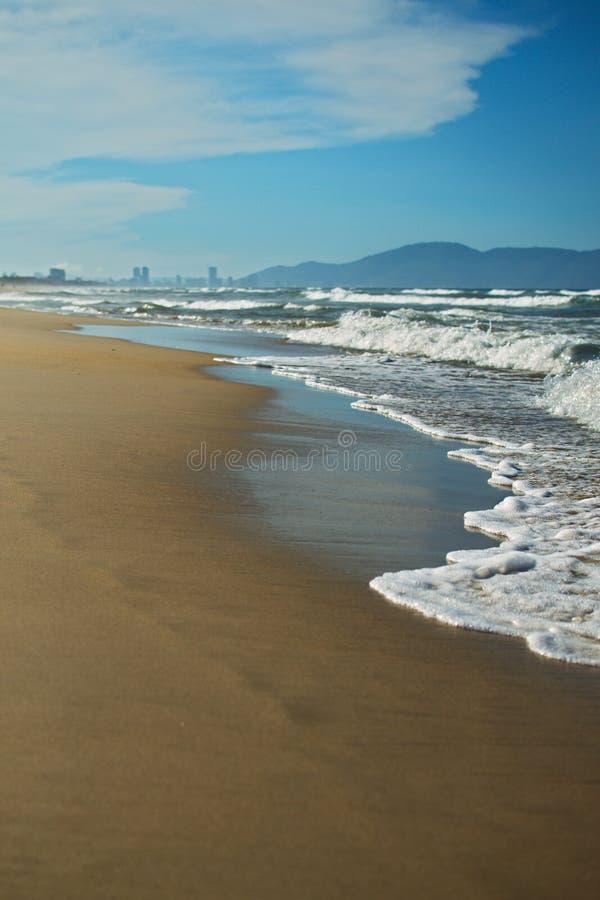 Plage sablonneuse, mer bleue avec la mousse de mer blanche et montagnes sur le fond de ciel bleu photos stock