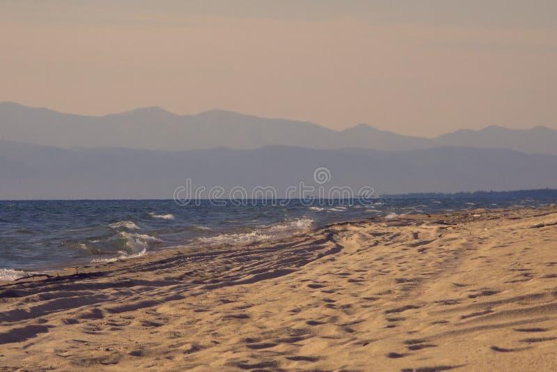 Plage sablonneuse s'étendant loin dans la distance et la silhouette des montagnes sur l'horizon dans un brouillard léger personne photographie stock libre de droits