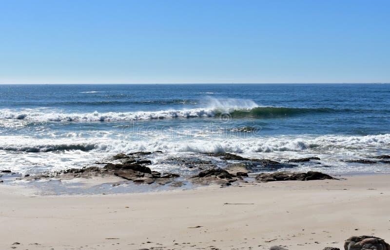 Plage sauvage avec des roches et la rupture de vagues Mer bleue avec la mousse, ciel clair Jour ensoleillé, Galicie, Espagne images stock