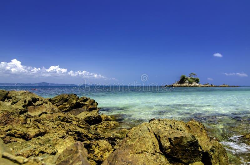 Plage tropicale à l'île de Kapas, Malaisie Roche humide et eau de mer clair comme de l'eau de roche avec le fond de ciel bleu images libres de droits