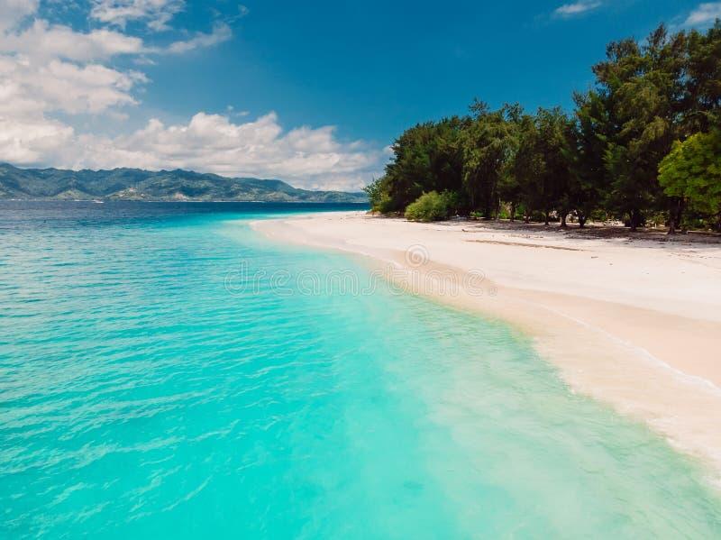 Plage tropicale avec l'océan de turquoise en île de paradis Silhouette d'homme se recroquevillant d'affaires images stock