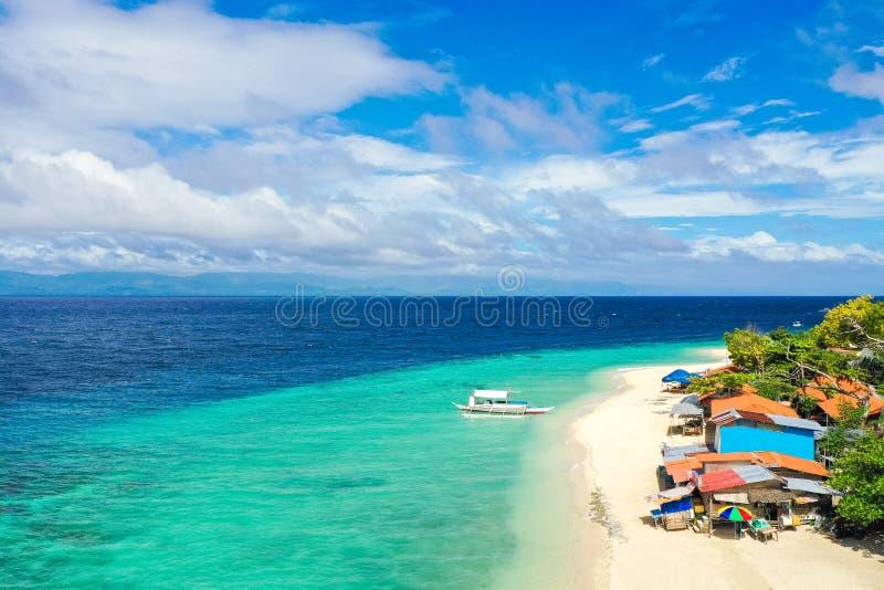 Plage tropicale avec la mer blanche de sable et de turquoise et toits des huttes locales Vue aérienne du bourdon photo libre de droits
