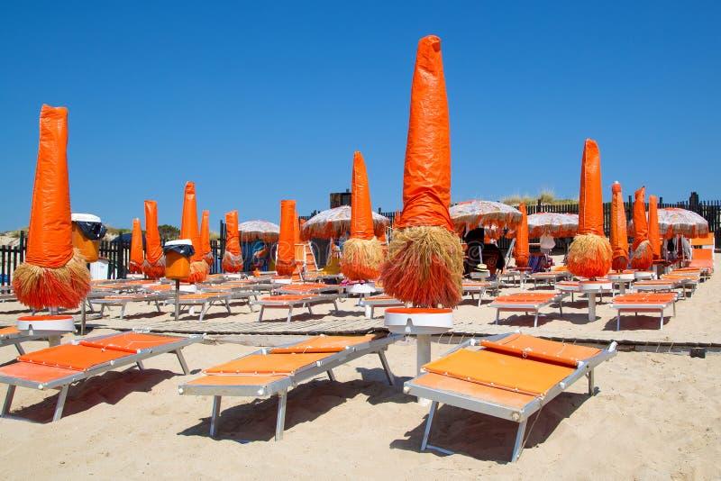 Plage vide avec les canapés oranges du soleil et les parapluies fermés images stock