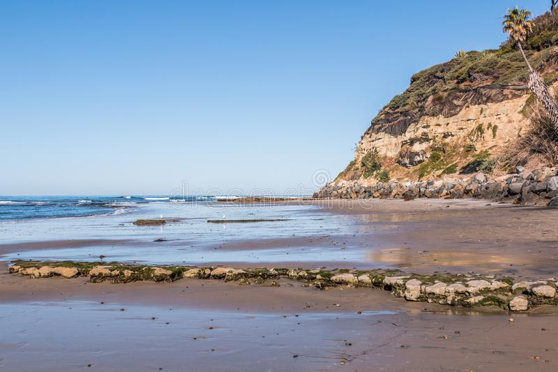 Plage vide du ` s de Swami à marée basse avec la falaise et le Rocky Reef images stock