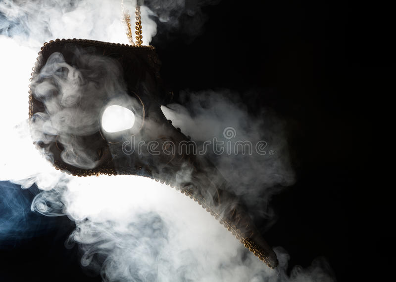 Plague mask hanging isolated with smoke vapor. On a black background stock photos