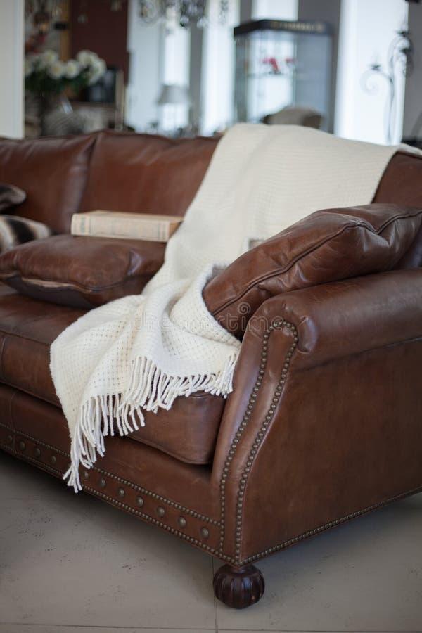 Plaid auf ledernem Sofa stockfoto