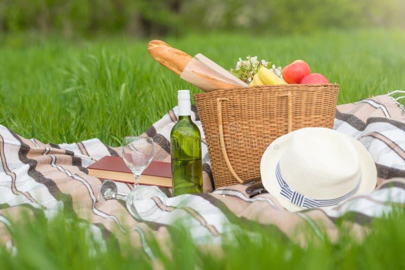 Plaid, chapeau, verres, livre, senvichi, jus et fruit avec un panier sur un plaid sur l'herbe verte Le concept d'un pique-nique,  images libres de droits