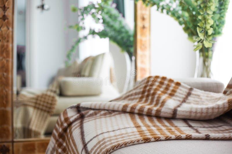 Plaid, das auf Sofa liegt stockbild