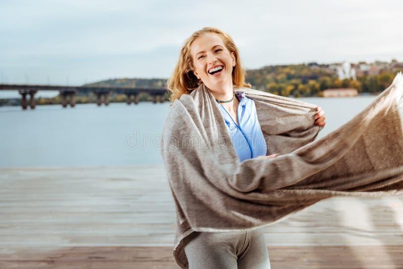 Plaid de port de jeune femme heureuse près de la rivière photographie stock