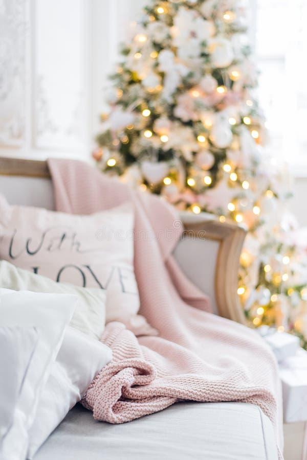 Plaid e cuscini tricottati su un sofà a casa su una notte di Natale Cosiness domestico immagine stock