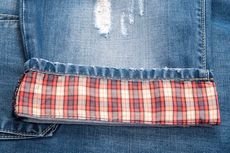 Plaid jeans. Fragments of plaid jeans, denim cloth close-up stock photos