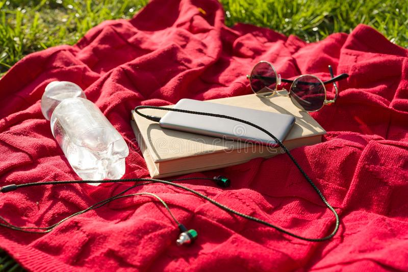 Plaid in the park - bottle of water, book, phone with headphones, sunglasses. Relax in the city park. stock photography