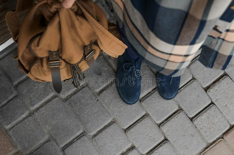 Plaid shirt, blue boots and brown backpack. stock photography