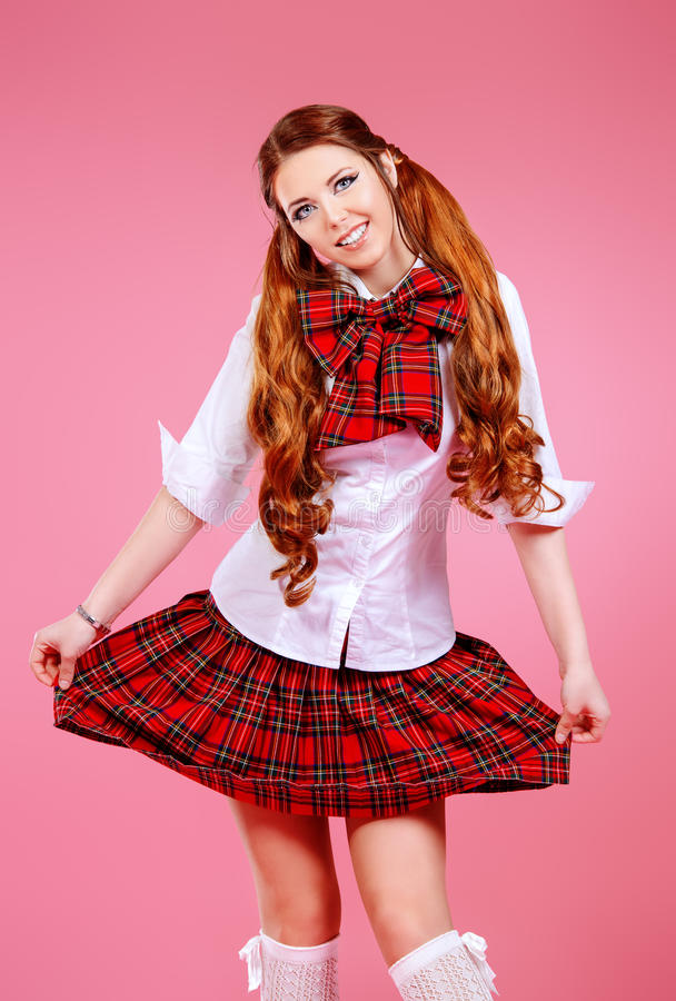Plaid skirt. Cute smiling teen girl in school plaid skirt and white blouse posing over pink background. Anime style stock images