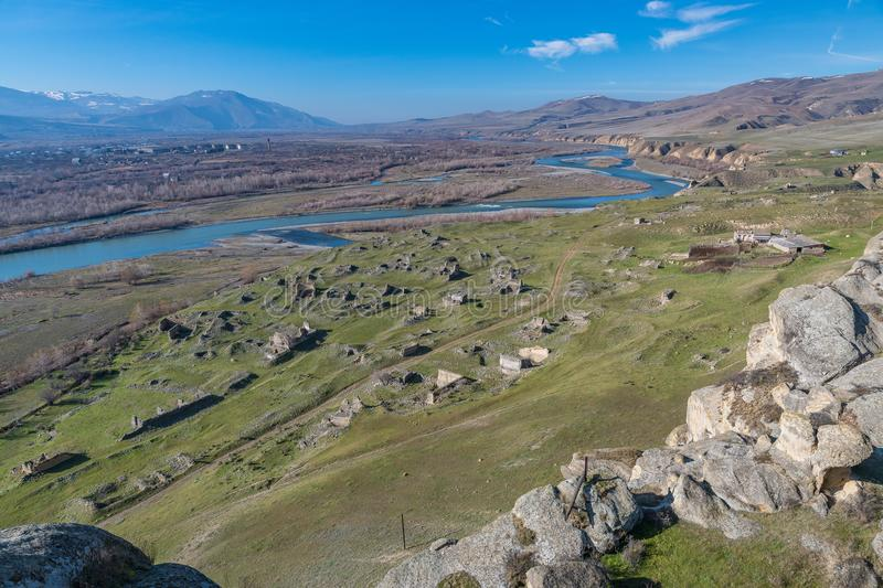 The plain below Uplistsikhe rock-hewn city. And Mtkvari river with the ruin of historic town below stock photography