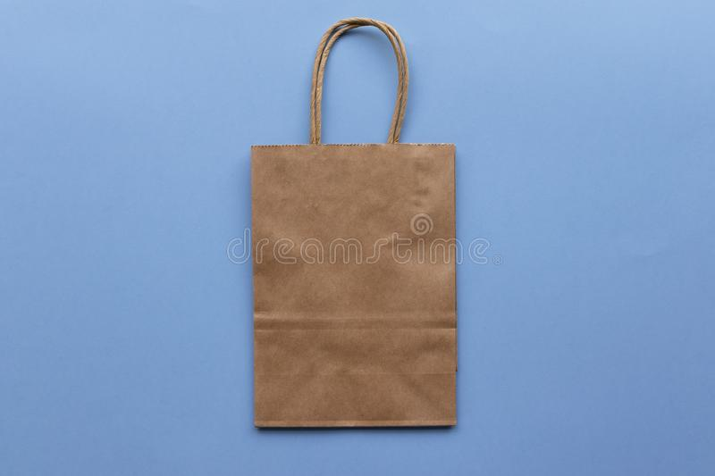 Plain blank brown paper bag on a blue background, empty for own design. Paper bag mock up stock photo
