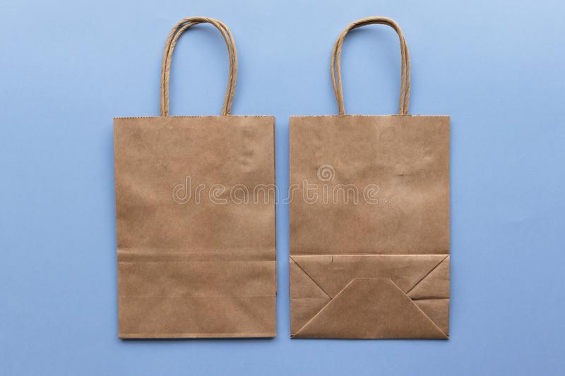Plain blank brown paper bag front and back on a blue background, empty for own design. Paper bag mock up stock photography