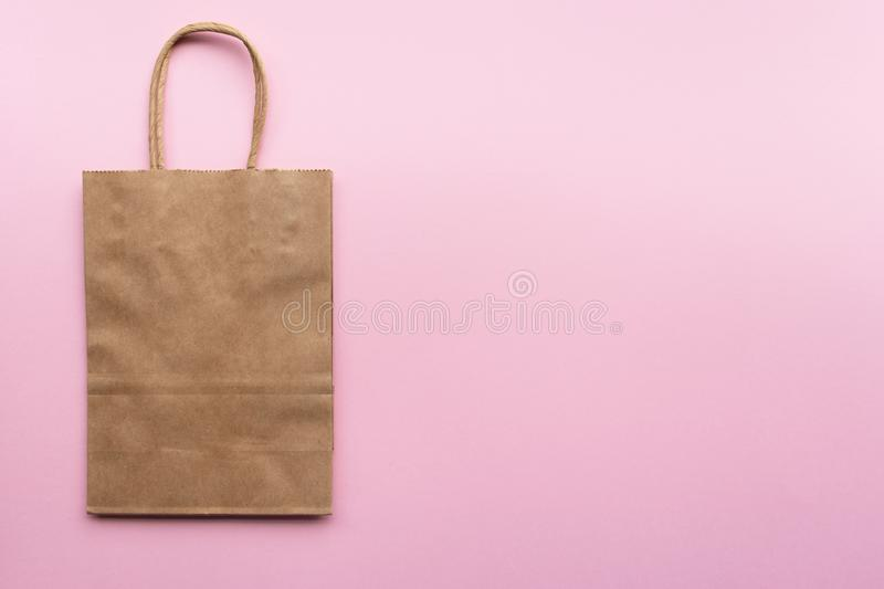 Plain blank brown paper bag on a pink background left, empty for own design. Paper bag mock up with copy space royalty free stock photos