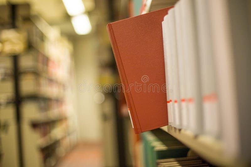 A plain book in a bookshelf. A plain red book in a bookshelf royalty free stock photos